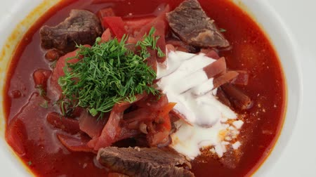 beef dishes : East European cuisine. Ukrainian red soup borscht with sour cream. Stock Footage