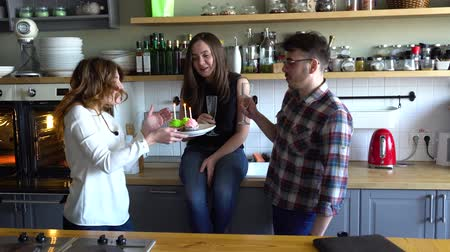 queque : two girls and guy blow out candles on the cupcake at the kitchen on muffine Vídeos
