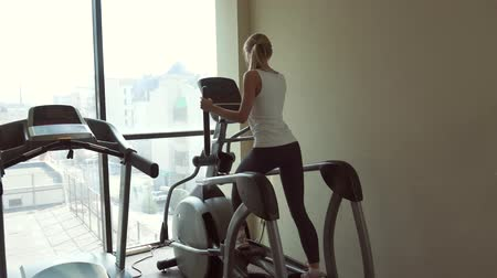 elliptical : Sports girl blonde is engaged on an ellipsoid near the window in gym back view Stock Footage