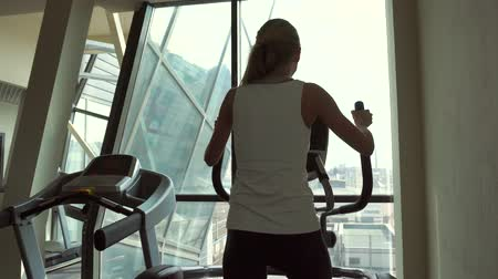 elliptical : Sports yonng woman blonde is engaged on an ellipsoid near the window back view Stock Footage