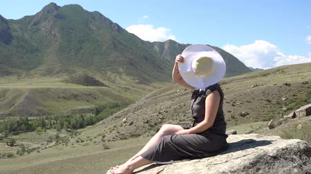 ouvido : A young girl with a toddler is throws a hat up with a happy expression on her face sitting on a rock in the background of the mountains.