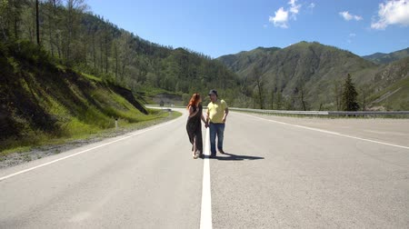 ouvido : Guy and girl are walking along the mountain road holding hands 4k.