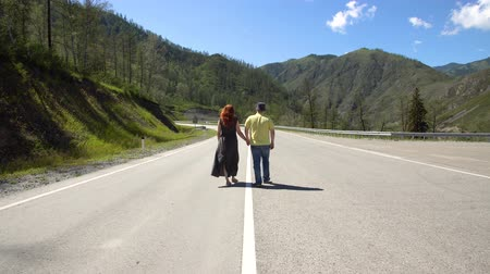ouvido : Beautiful couple of lovers walking along the road to the mountains holding hands 4k. Vídeos