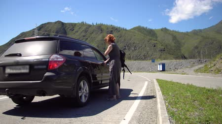 ouvido : A girl hitchhiking a car on a mountain road and sits down in it 4k.