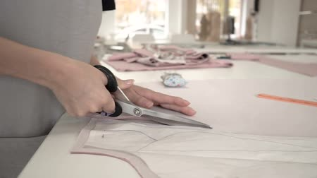 clothing : Fashion designer dresses 20s girl at work with scissors and cloth close-up HD. Stock Footage