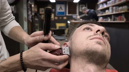 costeletas : Barber combs and cuts the sideburns of the client close-up 4k.
