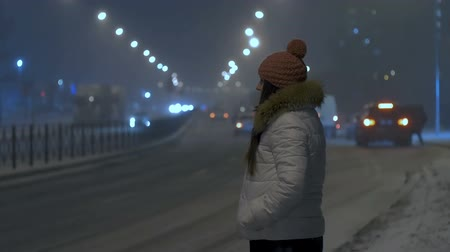 Strong night snowfall in city. Young girl crosses the road