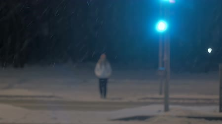 Strong night snowfall in city. People walk in snow