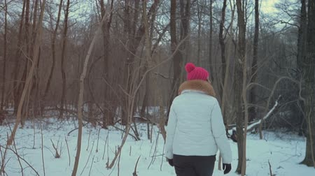 Young beautiful girl walking in winter forest