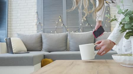 Young blonde puts the mug on the table and lay down on the sofa with a smartphone in hand Dostupné videozáznamy