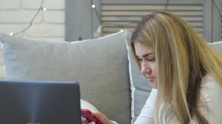 Young woman with smartphone and laptop lying on sofa at home. Dostupné videozáznamy