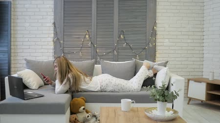pléd : Young woman with smartphone and laptop lying on sofa at home