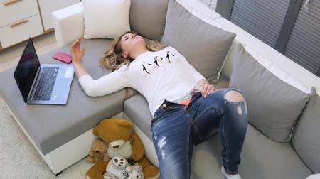 A young girl lay on the sofa. I could not wear my favorite jeans. Unsuitable size Dostupné videozáznamy