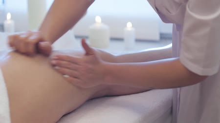 Young woman having feet massage in beauty spa salon, close up. Masseur kneads the foot and leg of a young beautiful girl at candle background. Close Up Shot