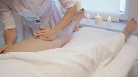 Young woman having feet massage in beauty spa salon. Masseur kneads the foot and leg of a young beautiful girl at candle background. Close Up Shot