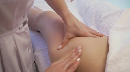 massagista : Young woman having feet massage in beauty spa salon. Masseur kneads the foot and leg of a young beautiful girl. Close Up Shot Vídeos