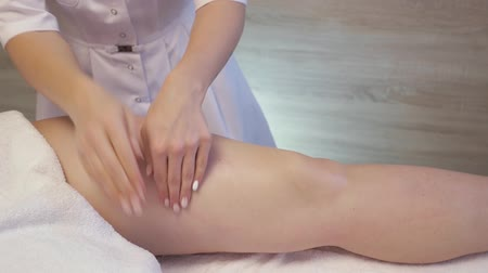 Young woman having feet massage in beauty spa salon. Masseur kneads the foot and leg of a young beautiful girl. Close Up Shot Dostupné videozáznamy