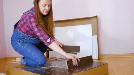 trousers : Assembly of white bedroom furniture, pregnant girl collects wood furniture in the flat. Moving to a new apartment concept. Medium Shot Stock Footage