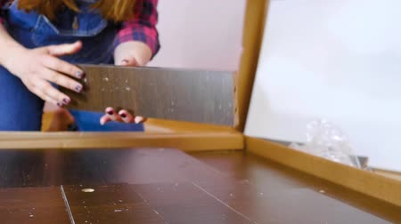 trousers : Assembly of bedroom furniture, pregnant girl collects wood furniture in the flat. Moving to a new apartment concept. Close Up Shot Stock Footage