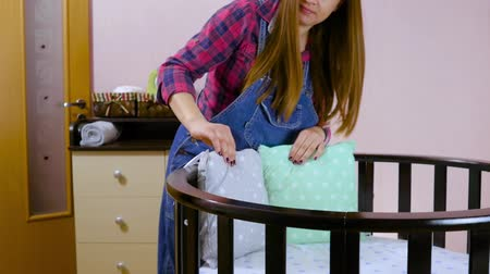 trousers : A pregnant woman in preparation for a newborn child is prepared for the meeting. Folding childrens wooden furniture, cradles, crib, pillows. Build furniture - baby cot. Medium shot. Stock Footage
