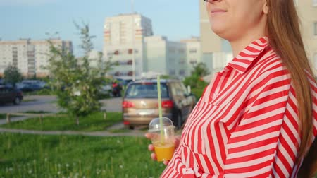 bekleyen : Pregnant woman in red dress waiting for a child. Woman drinking orange juice and walking on the city. The concept of tenderness pregnancy and motherhood. Close up shot.