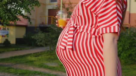 tutmak : Pregnant woman waiting for a child. Woman keep a glass with juice and walking on the city. The concept of tenderness pregnancy and motherhood. Close up shot. Stok Video