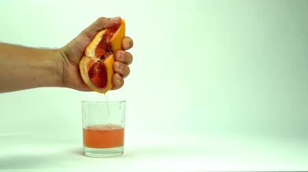 antioxidant : man squeezing half of juicy grapefruit to empty glass on white background, close up Stock Footage