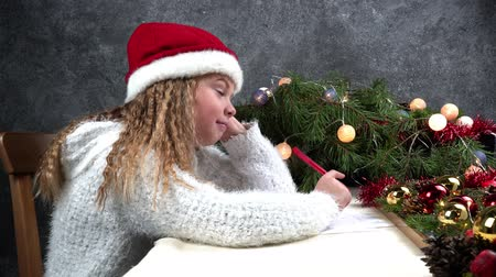 small pen : Little girl writes a letter to Santa Claus. Emotions: joy, happiness, thoughtfulness, fatigue ... Christmas should be hurried soon for Santa to make dreams come true