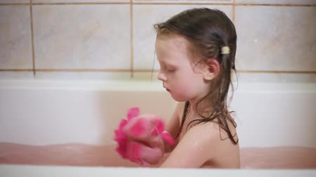 wanna : The little girl is washed in the bathroom with a red washcloth. Wideo