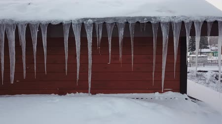 melts : Winter icicles hang on the roof.