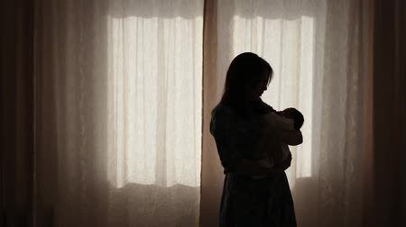 новорожденный : A young mother cradles a child. In the background is a window. Стоковые видеозаписи