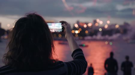 Women taking pictures of Fireworks Display. video and photo technology crowd holidays memories 4k. Beautiful moving particles background and glitter USA 4th of July New Year Celebration