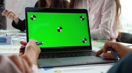 lupetto : Close-up of a Mans Hands Working on Green Screen on a Laptop.In the background, people are sitting at the table and talking. The team discusses the project in the office.