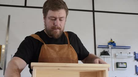 A man with a beard works in his workshop. Profession carpenter. A man works with a tree. The carpenter takes measurements, saws, planes, drills wooden products in a bright workshop. Dostupné videozáznamy