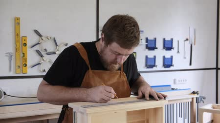 drilling wood : A man with a beard works in his workshop. Profession carpenter. A man works with a tree. The carpenter takes measurements, saws, planes, drills wooden products in a bright workshop. Stock Footage