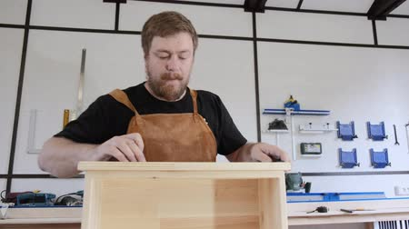 A man with a beard works in his workshop. Profession carpenter. A man works with a tree. The carpenter takes measurements, saws, planes, drills wooden products in a bright workshop. Stockvideo