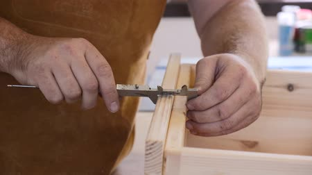 Close-up. A carpenter with a caliper makes measurements. A man works with a tree. The carpenter takes measurements, saws, planes, drills wooden products in a bright workshop. Dostupné videozáznamy