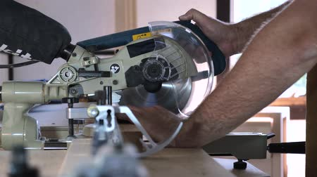 Close-up. Hands of a carpenter lower a circular saw on a wooden block. Slow motion.