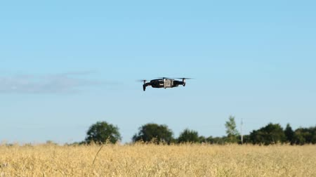 Quadrocopter is hanging in the air. In the background is a field and blue sky.