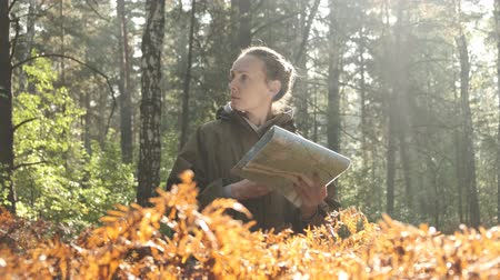 navigational : Young girl in forest, looking at camera, thinking, dreaming, nature background, concept 60 fps. Woman with old map in forest. Young beautiful woman hiking on a forest. Closeup portrait shot 4k Stock Footage