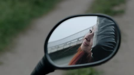 rider : The red-haired girl takes off the helmet from the head. Reflection through the mirror of a motorcycle. Slow motion.
