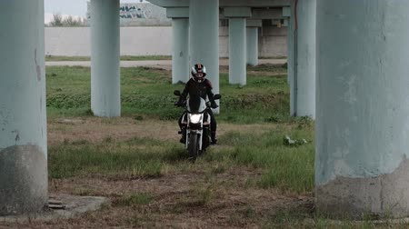 байкер : Girl on a motorcycle rides through the grass. Стоковые видеозаписи