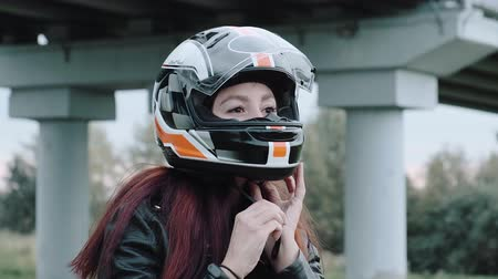 moto trials : Redhead girl puts a motorcycle helmet on her head. Girl in a leather jacket sitting on a motorcycle getting ready for the trip. The concept of freedom, travel, action.