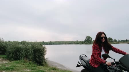 věčnost : A young beautiful, happy girl rides a motorcycle to the lake and looks around. Concept: freedom and eternity. 4K slow motion.