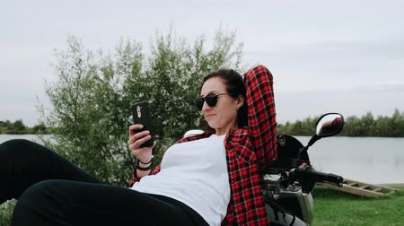 nóbl : Young girl takes a selfie while lying on a motorcycle by the lake. 4K Slow motion. The concept of freedom, travel, action.