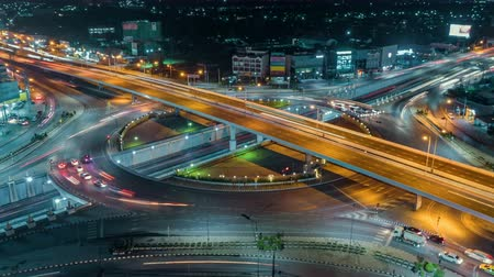 interscambio : timelapse of night city traffic on 4-way stop street intersection circle roundabout in bangkok at night, thailand. 4K UHD horizontal aerial view. Filmati Stock