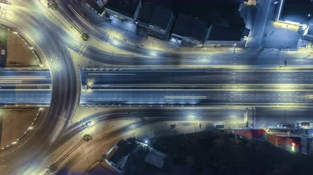 csomópont : Hyperlapse timelapse of night city traffic on 4-way stop street intersection circle roundabout in bangkok, thailand. 4K UHD horizontal aerial view.