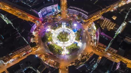 yaymak : Hyperlapse timelapse moving go right circular of night city traffic on 4-way stop street intersection circle roundabout in bangkok thailand at night, 4K UHD horizontal aerial view.