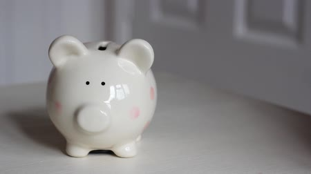 bancos : Girl Puts Pound Coins into Piggy Bank