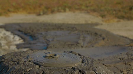выброс : Close-up shot of a slow eruption of volcano mud.